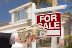 home for sale sign and hand holding cash